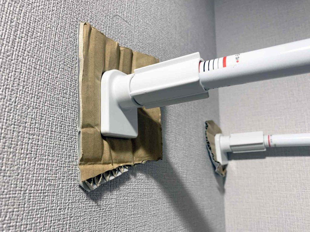 突っ張り棒で壁紙に凹み跡がつかないようにダンボールを挟んだ状態