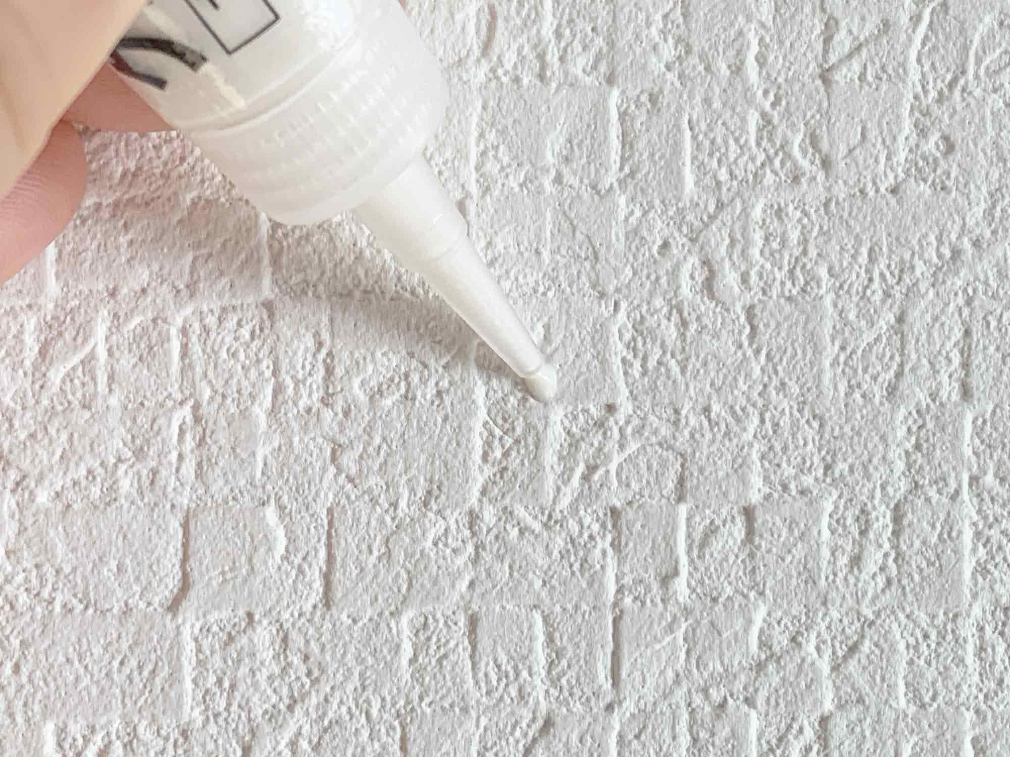 壁に開いた画鋲の穴にパテで補修する様子