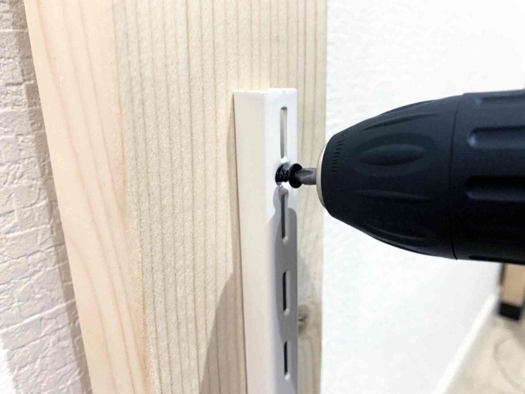 電動ドリルで棚の支柱に付属のネジを2×4材に組み込む