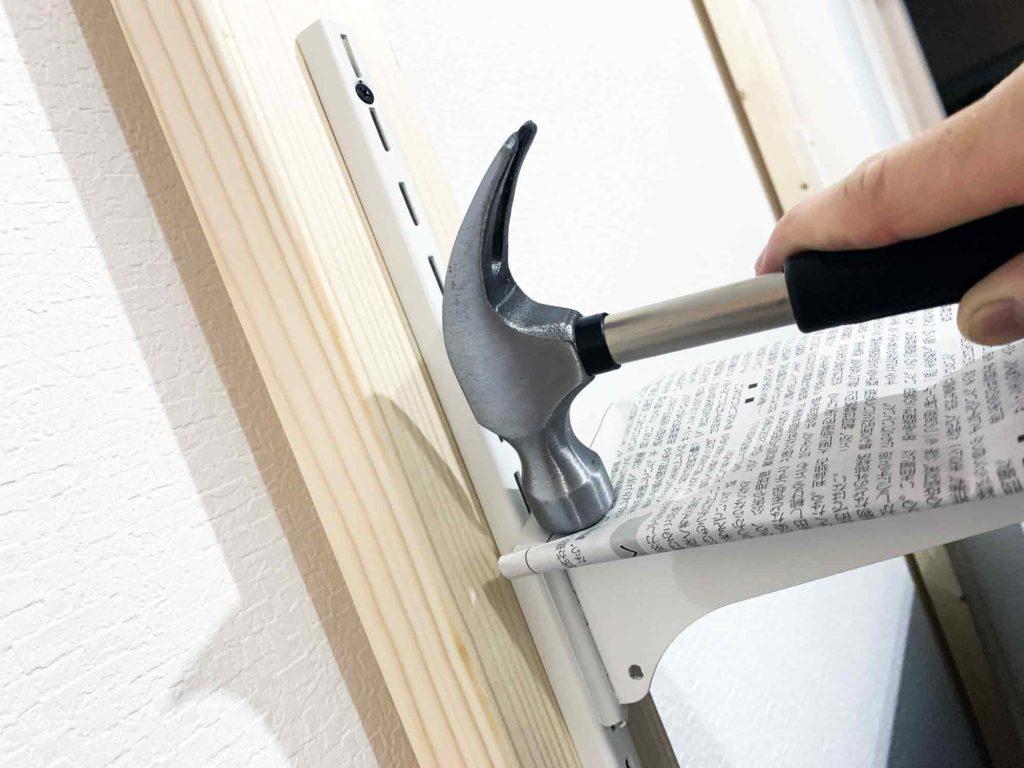 2×4材の支柱に棚受けを差し込む。新聞紙を挟んで金槌で叩くと傷つかない