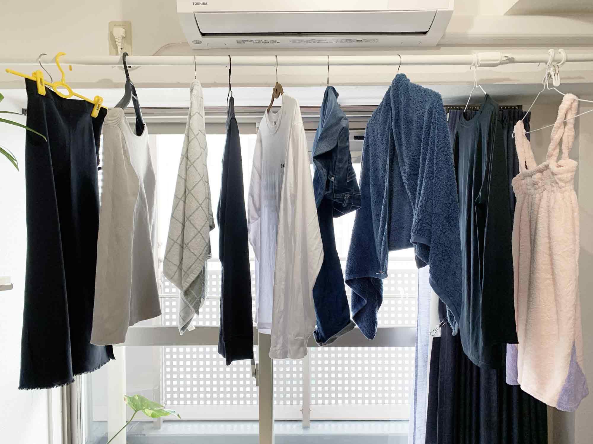 突っ張り棒に洗ったばかりで重い洗濯物を掛けて部屋干し