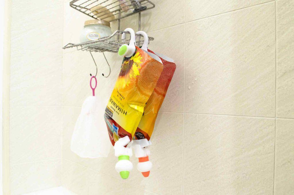 シャワーラックにシャンプーとコンディショナーの詰め替え用パッケージを吊るす
