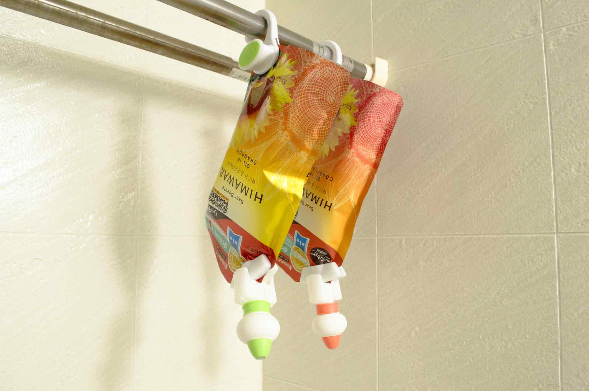 浴室乾燥機の洗濯物を吊るす棒にシャンプーとコンディショナーの詰め替え用パッケージを吊るす
