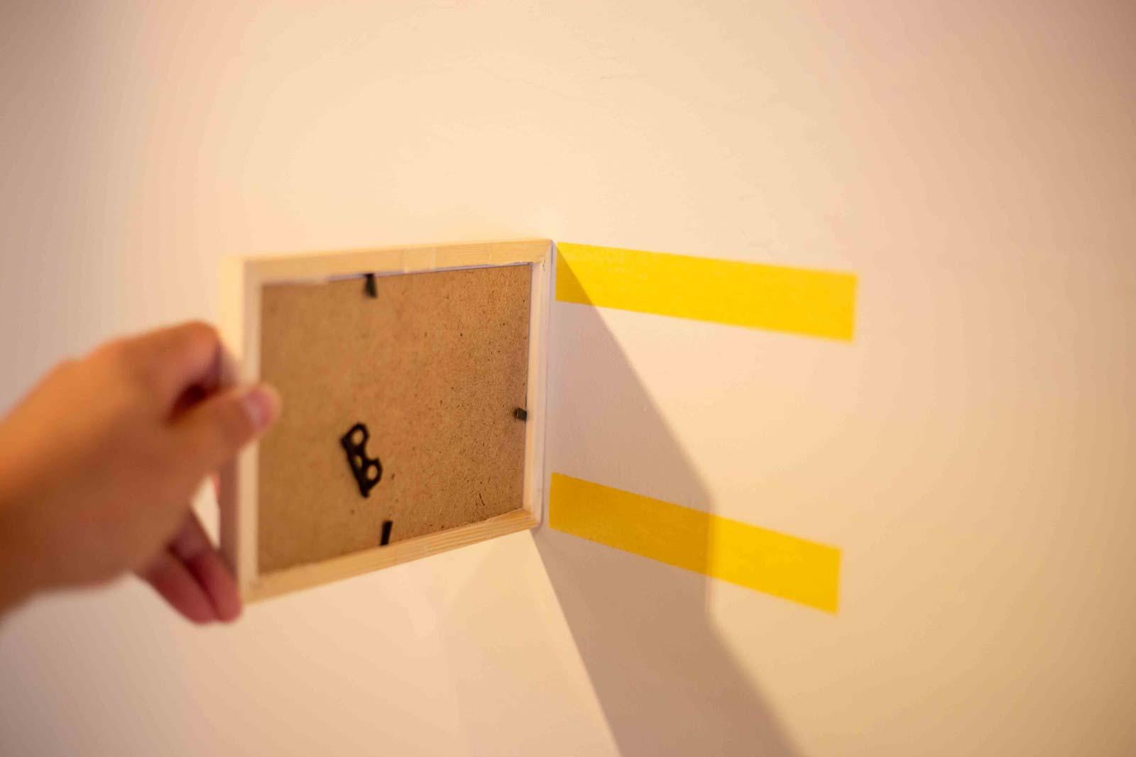 壁に貼り付けたマスキングテープの位置にフォトフレームを貼り付ける。位置がずれるとはみ出てしまうので注意が必要