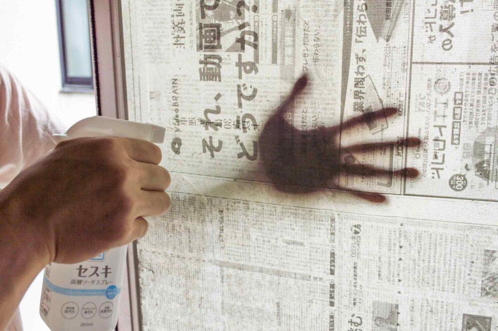 新聞紙を広げた網戸の裏側からセスキ炭酸ソーダを吹きかける