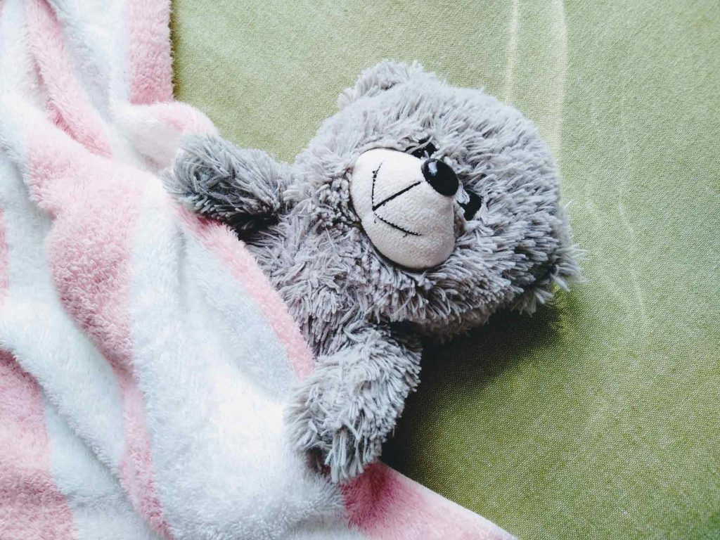 クマのぬいぐるみが布団に入って寝ている