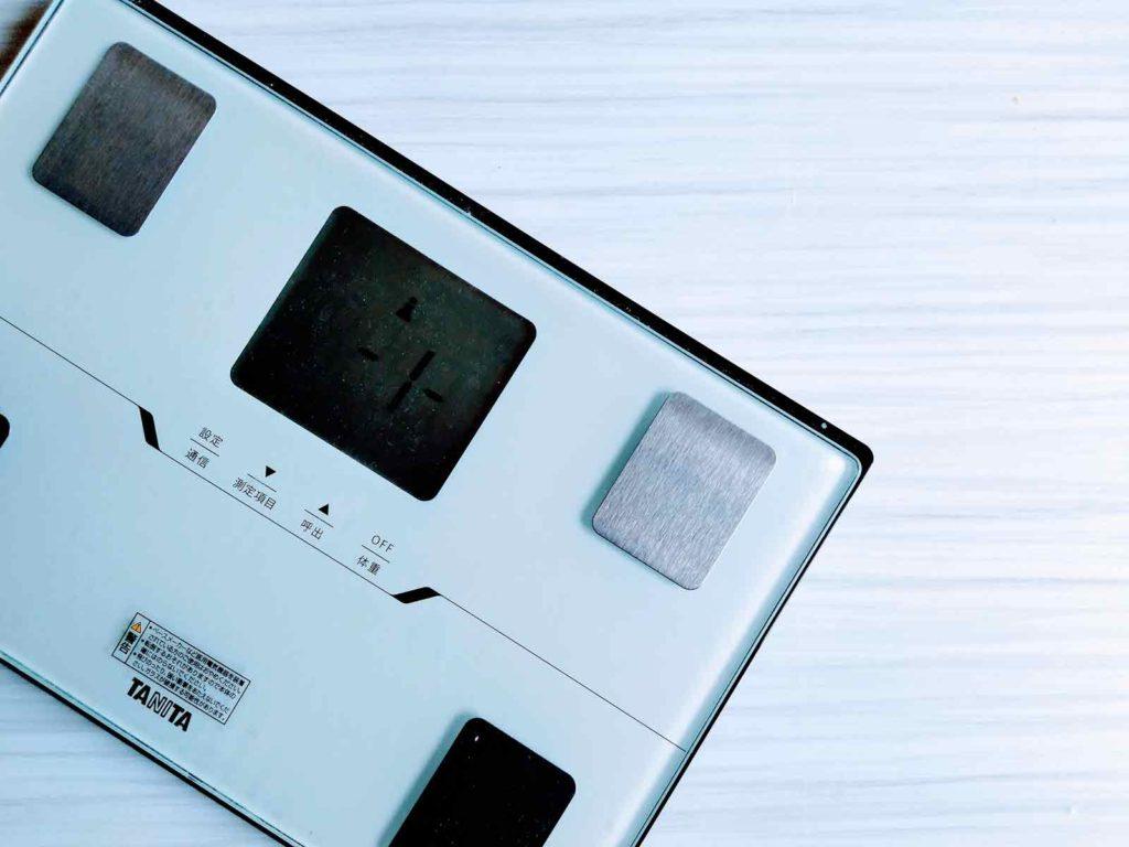 白い台の上にシンプルなデザインの体重計が乗っている